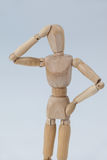 Confused wooden figurine standing with hand on head Royalty Free Stock Photography