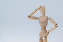 Confused wooden figurine standing with hand on head Stock Images