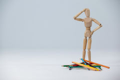 Confused wooden figurine standing near a heap of color pencils Stock Images