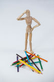 Confused wooden figurine standing near a heap of color pencils Stock Photos
