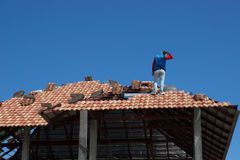 Confused worker on roof. Confused worker work on tile arrangement on home roof construction Royalty Free Stock Images