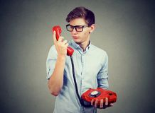 Confused worried man looking at old fashioned telephone. Confused worried teenager man wearing glasses looking at old fashioned red telephone Royalty Free Stock Photo