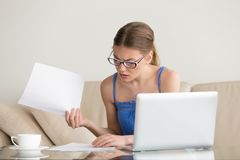 Confused worried woman looks through papers, having problem with Stock Photos