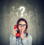 Confused worried woman talking on a phone has many questions royalty free stock photo