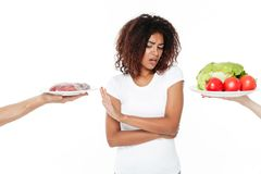 Confused young african woman choosing between meat and vegetables. Picture of confused young african woman standing isolated over white background. Choosing Royalty Free Stock Image