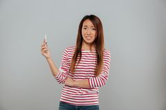 Confused young asian lady talking by phone. Image of confused young asian lady talking by phone standing isolated over grey wall. Looking camera Royalty Free Stock Photo