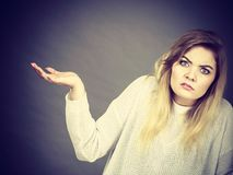 Confused young blonde woman gesturing with hands stock photo