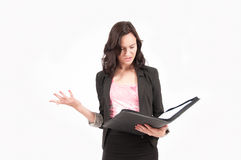 Confused Young Brunette European Business Woman. Photo of a young brunette European business woman looking through her notes in a folder and looking confused and Stock Image