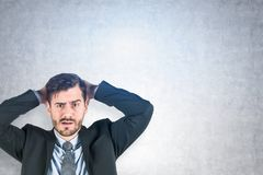 Confused young businessman, concrete wall stock photos