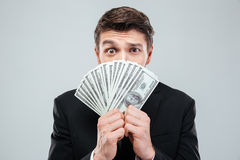 Confused young businessman covered his face with money Royalty Free Stock Photography