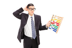 Confused young businessman holding an abacus Stock Photo