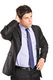 Confused young businessman looking in the distance. Isolated on white background Royalty Free Stock Image