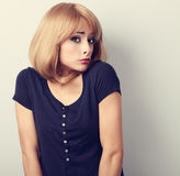 Confused young casual woman with blond hair. Stock Image
