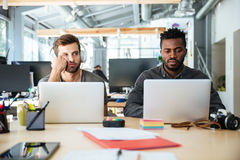 Confused young colleagues sitting in office coworking Royalty Free Stock Photo