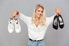 Confused young girl choosing shoes Royalty Free Stock Photos