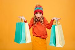 Confused Young girl in sweater and hat holding packages. While looking at the camera over orange background stock photography
