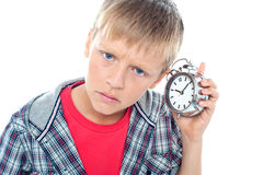 Confused young kid holding time piece Royalty Free Stock Image