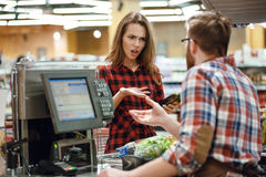 Confused young lady standing in supermarket shop. Photo of confused young lady standing in supermarket shop near cashier`s desk. Looking aside Stock Photos