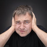 Confused young man in black T-shirt. Royalty Free Stock Image