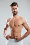 Confused young man dissatisfied with the excess weight. Royalty Free Stock Photo