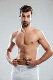 Confused young man dissatisfied with the excess weight. Royalty Free Stock Images