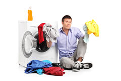 Confused young man doing laundry Royalty Free Stock Photography