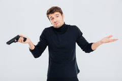 Confused young man with gun shrugging his shoulders Royalty Free Stock Photo