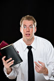 Confused young man holding bibles Stock Photography
