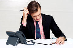 Confused young man itching his head with pen Stock Image