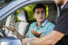 Confused young man. Confused young men in the car stopped by policeman stock images
