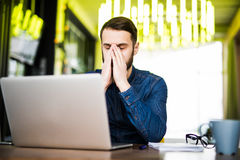 Confused young man sitting near laptop and holding head with his hand. Looking at laptop. Royalty Free Stock Image