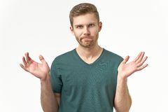 Confused young man spreads hands in different sides, feels uncertain, wears casual t shirt. Being puzzled by unexpected event. Poses over white blank studio stock image