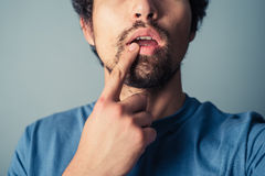 Confused young man. Touching his lip with his finger royalty free stock images
