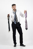 Confused young man trying to choose right necktie. Royalty Free Stock Photos