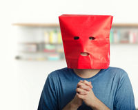 Confused young man wears red paper bag royalty free stock images