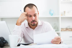 Confused young man at workplace Stock Photo