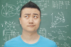 Confused young student in front of blackboard with math equations, making a face Stock Photography