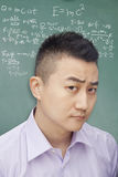 Confused young student in front of blackboard with math equations, making a face, portrait Stock Images