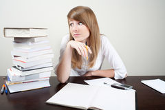 Confused young woman. Confused student sitting at table with books Royalty Free Stock Photo