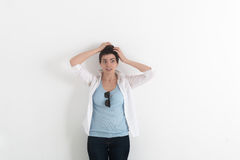 The confused young woman has clasped hands a head on white background Royalty Free Stock Image