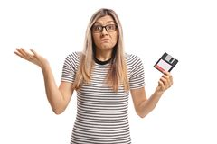 Confused young woman holding a floppy disk. Isolated on white background Stock Photography