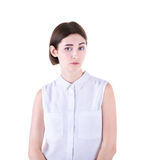 A confused young woman isolated on a white background. A cute brunette girl is surprised and bewildered. Human face expressions. Royalty Free Stock Images