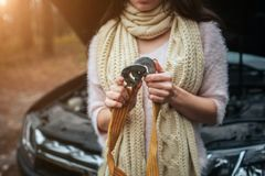 Confused young woman looking at broken down car engine car repair on the street.  Royalty Free Stock Images