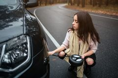 Confused young woman looking at broken down car engine car repair on the street.  Stock Image