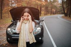 Confused young woman looking at broken down car engine car repair on the street.  Stock Photos