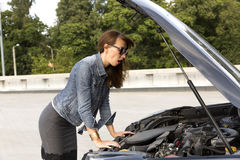 Confused young woman looking at broken down car engine on street Stock Photography