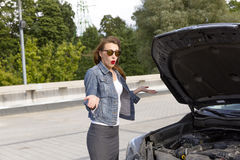 Confused young woman looking at broken down car engine on street Royalty Free Stock Image