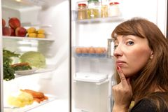 Confused young woman looking in fridge. At kitchen stock images