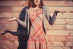 Confused young woman outside wooden cabin Stock Image