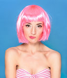 Confused young woman with pink hair on a blue background Stock Image